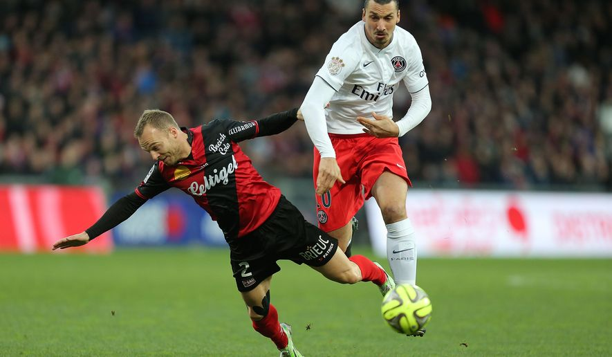 Paris Saint Germain's forward Zlatan Ibrahimovic of Sweden challenges for the ball with Guingamp's defender Lars Jacobsen during their League One soccer match, in Guingamp, western France, Sunday, Dec. 14 , 2014. (AP Photo/David Vincent)