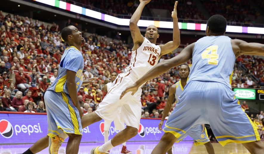 Iowa State guard Bryce Dejean-Jones, center, shoots between Southern University's Adrian Rodgers, left, and Keith Davis, right, during the first half of an NCAA college basketball game, Sunday, Dec. 14, 2014, in Ames, Iowa. (AP Photo/Charlie Neibergall)