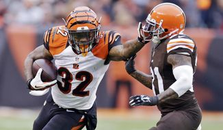 Cincinnati Bengals running back Jeremy Hill (32) runs against Cleveland Browns strong safety Donte Whitner in the second quarter of an NFL football game Sunday, Dec. 14, 2014, in Cleveland. (AP Photo/Tony Dejak)