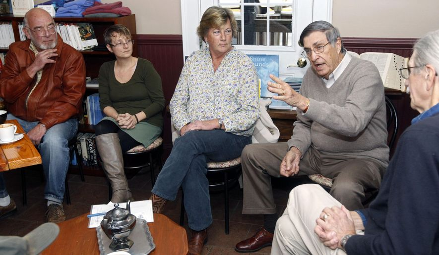 ADVANCE FOR MONDAY DEC. 14 AND THEREAFTER This Dec. 4, 2014 photo shows Scottsville mayor, Barry Grove, left, Chamber of Commerce president Petra Monaco, second from left, Pam Steven, center,  Larry Barnett and Ron Smith, right, talk about the economic forecast for the town of Scottsville at Baine's Books & Coffee in Scottsville, Va. Finding businesses to fill vacant storefronts is a concern for any community, but officials and business leaders in Albemarle County's only incorporated town say they have a concern that's even greater. (AP Photo/The Daily Progress, Ryan Kelly)