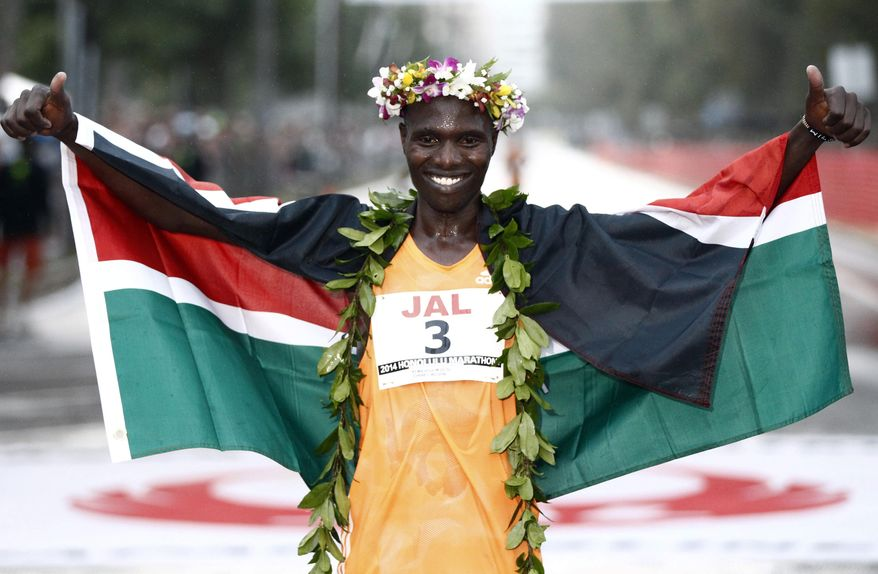 Men's first place finisher Wilson Chebet, of Kenya, poses for photos after the 2014 Honolulu Marathon on Sunday, Dec. 14, 2014 in Honolulu, Hawaii. (AP Photo/The Honolulu Advertiser, Jamm Aquino)