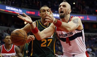 Washington Wizards center Marcin Gortat (4), from Poland, loses control of the ball against Utah Jazz center Rudy Gobert (27), from France, in the first half of an NBA basketball game, Sunday, Dec. 14, 2014, in Washington. (AP Photo/Alex Brandon)