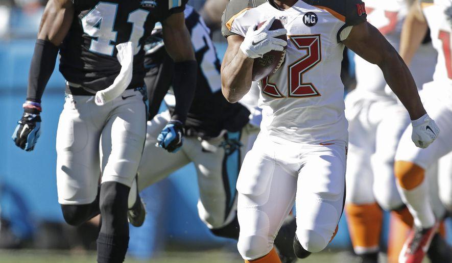 Tampa Bay Buccaneers' Doug Martin (22) runs past Carolina Panthers' Roman Harper (41) in the first half of an NFL football game in Charlotte, N.C., Sunday, Dec. 14, 2014. (AP Photo/Bob Leverone)