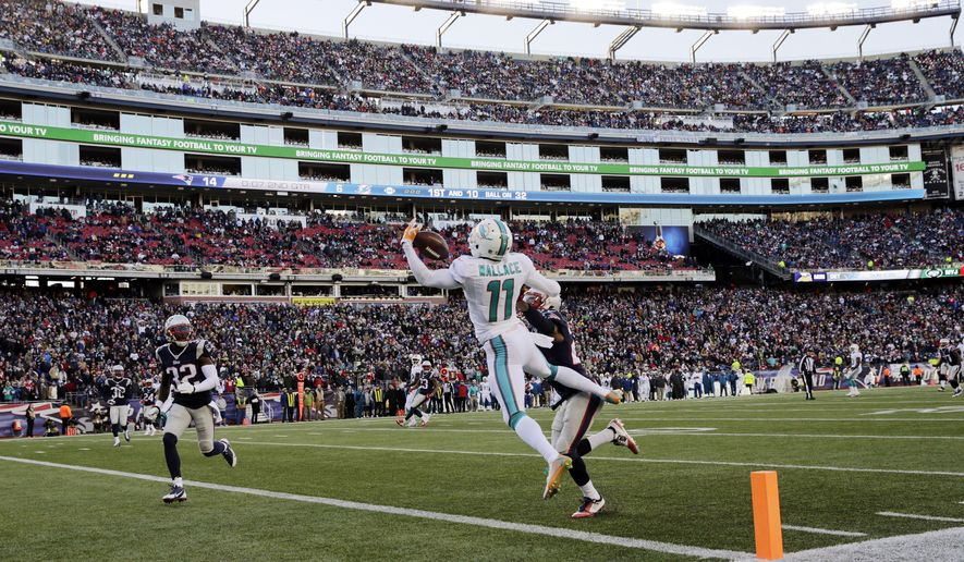 Miami Dolphins wide receiver Mike Wallace (11) catches a touchdown pass in front of New England Patriots defensive back Malcolm Butler, right rear, and safety Devin McCourty (32) in the first half of an NFL football game, Sunday, Dec. 14, 2014, in Foxborough, Mass. (AP Photo/Charles Krupa)