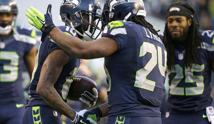 Seattle Seahawks wide receiver Paul Richardson, left, is congratulated on his first NFL touchdown by teammate Marshawn Lynch, center, as Richard Sherman looks on at right in the second half of an NFL football game against the San Francisco 49ers, Sunday, Dec. 14, 2014, in Seattle. (AP Photo/Elaine Thompson)