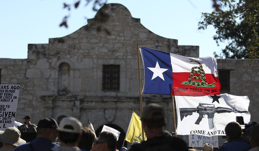 "In this Oct. 19, 2013, file photo, flags fly at the ""Come And Take It San Antonio"" rally. (AP Photo/San Antonio Express-News, Kin Man Hui, File)"