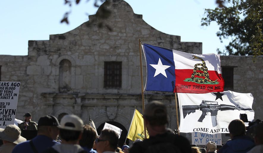 """FILE - In this Oct. 19, 2013 file photo, flags fly at the """"Come And Take It San Antonio"""" rally. Long depicted as the rootin'-tootin' capital of American gun culture, Texas is one of the few states with an outright ban on the open carry of handguns. That could change next year, with an expected push for expanding gun rights from the Republican-dominated Legislature. (AP Photo/San Antonio Express-News, Kin Man Hui, File)"""