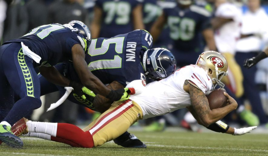 San Francisco 49ers quarterback Colin Kaepernick (7) is sacked in the second half of an NFL football game by Seattle Seahawks outside linebacker Bruce Irvin (51) and Kam Chancellor, left, Sunday, Dec. 14, 2014, in Seattle. (AP Photo/John Froschauer)