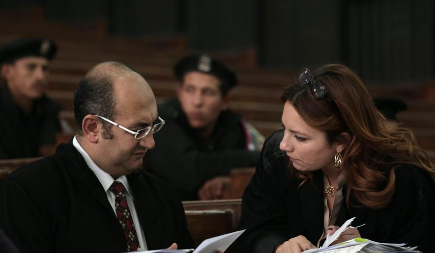 In this Thursday, Dec. 4, 2014 photo, Egyptian lawyer Ragia Omran, right, speaks with lawyer Khaled Ali, during a trial session of activists facing charges on organizing unauthorized protests, at a courtroom in Cairo, Egypt. Revolution supporters have been left demoralized. Some are in prison, some have left the country. Some, as Omran puts, are getting married and trying to live their lives. Others, like Omran and human rights lawyers doing similar work, are simply doing what they can. (AP Photo/Nariman El-Mofty)