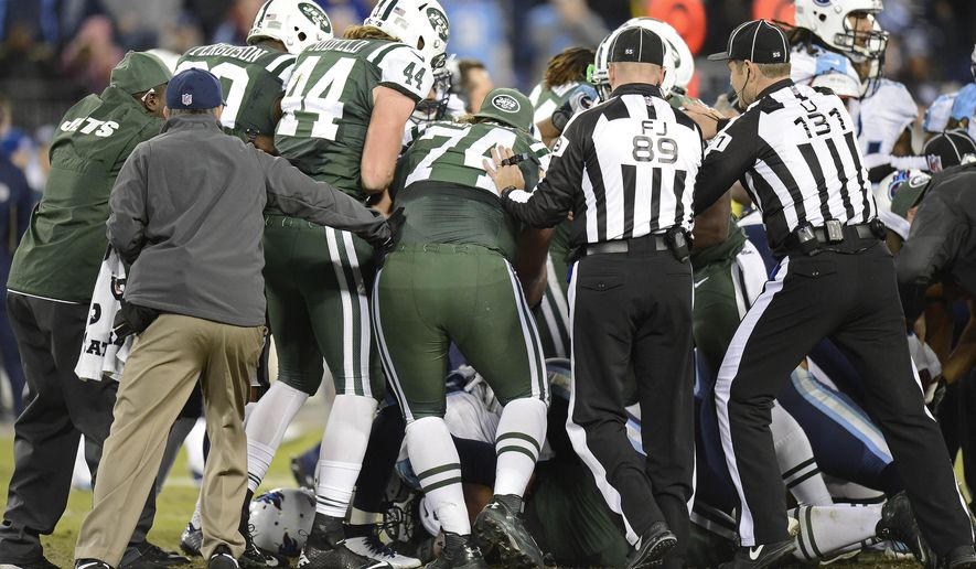 Officials try to break up a fight between players in the second half of an NFL football game between the Tennessee Titans and the New York Jets, Sunday, Dec. 14, 2014, in Nashville, Tenn. (AP Photo/Mark Zaleski)