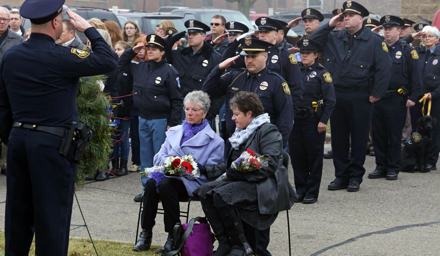 Law enforcement officers salute to Grand Haven police officer Scott Flahive as his mother, Lin Emmert, and sister, Lisa Hoier, are seated before them Saturday, Dec. 13, 2014, during a ceremony commemorating the 20th anniversary of the shooting death of Flahive in front of the Grand Haven Eagles building downtown Grand Haven. (AP Photo/The Muskegon Chronicle, Andraya Croft)