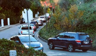 This Tuesday, Dec. 9, 2014 early morning rush hour traffic winds it's way along a narrow street in Sherman Oaks section of Los Angeles. When the people whose houses hug the narrow warren of streets paralleling the busiest urban freeway in America began to see bumper-to-bumper traffic rushing by their homes a year or so ago they were baffled. When word spread that the explosively popular new smartphone app Waze was sending many of those cars through their neighborhood in a quest to shave five minutes off a daily rush-hour commute, they were angry and ready to fight back. (AP Photo/Richard Vogel)