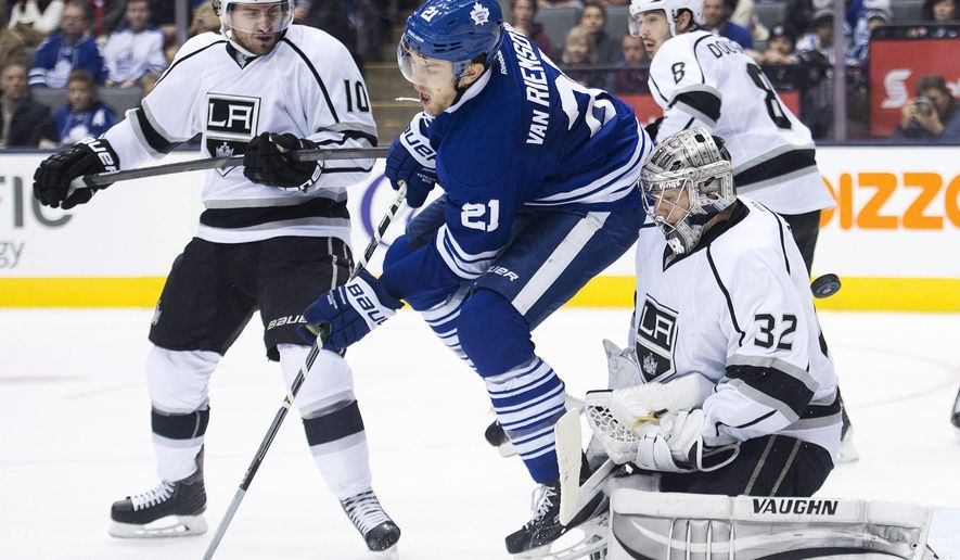 Los Angeles Kings goalie Jonathan Quick (32) makes a save on a tip by Toronto Maple Leafs forward James van Riemsdyk (21) as Kings forward Mike Richards (10) hooks him up during second period of an NHL hockey game in Toronto, Sunday, Dec. 14, 2014. (AP Photo/The Canadian Press, Nathan Denette)