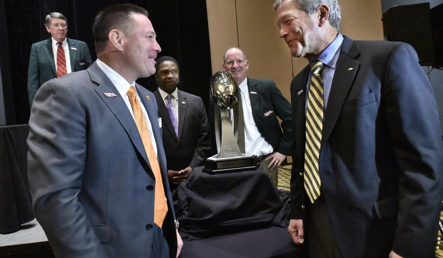 Coaches of the TaxSlayer Bowl, University of Tennessee football coach Butch Jones and University of Iowa football coach Kirk Ferentz talk after a news conference Thursday, Dec. 11, 2014 in Jacksonville, Fla. (AP Photo/The Florida Times-Union, Will Dickey)