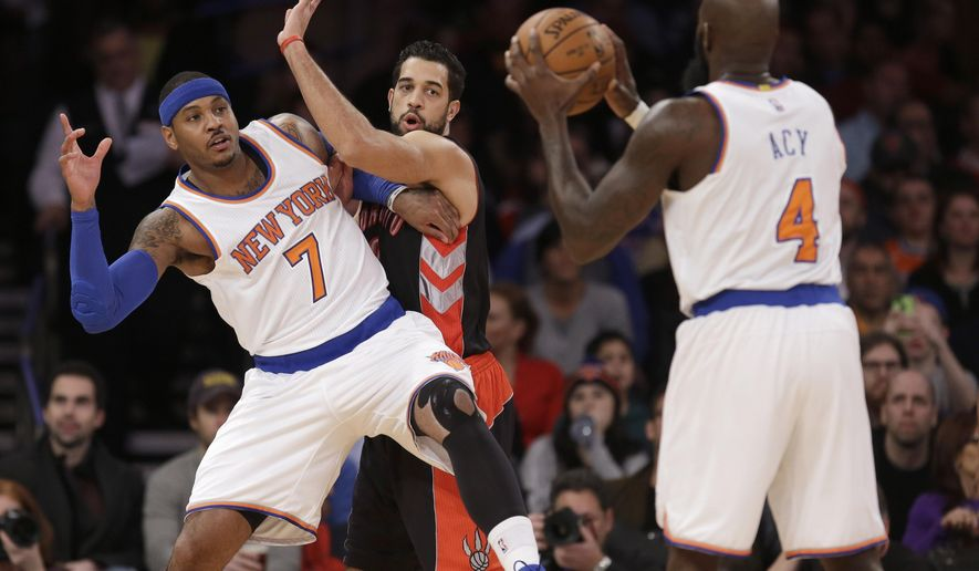 New York Knicks' Carmelo Anthony, left, looks for a pass from Quincy Acy, right, while Toronto Raptors' Landry Fields defends during the first half of an NBA basketball game, Sunday, Dec. 14, 2014 in New York. (AP Photo/Seth Wenig)
