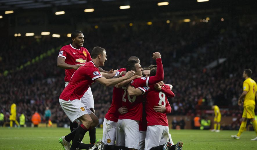 Manchester United's Robin van Persie, lower centre, celebrates with teammates after scoring during the English Premier League soccer match between Manchester United and Liverpool at Old Trafford Stadium, Manchester, England, Sunday Dec. 14, 2014. (AP Photo/Jon Super)