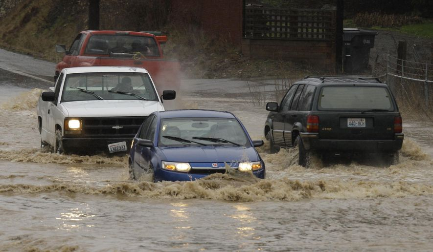 FILE - In this Jan. 7, 2009 file photo, cars drive on a flooded road in Orting, Wash. As storms threaten to flood rivers throughout the Northwest again in late 2014, flood-control managers are increasingly turning to more natural approaches to keep rivers from overtopping. (AP Photo/Ted S. Warren, file)