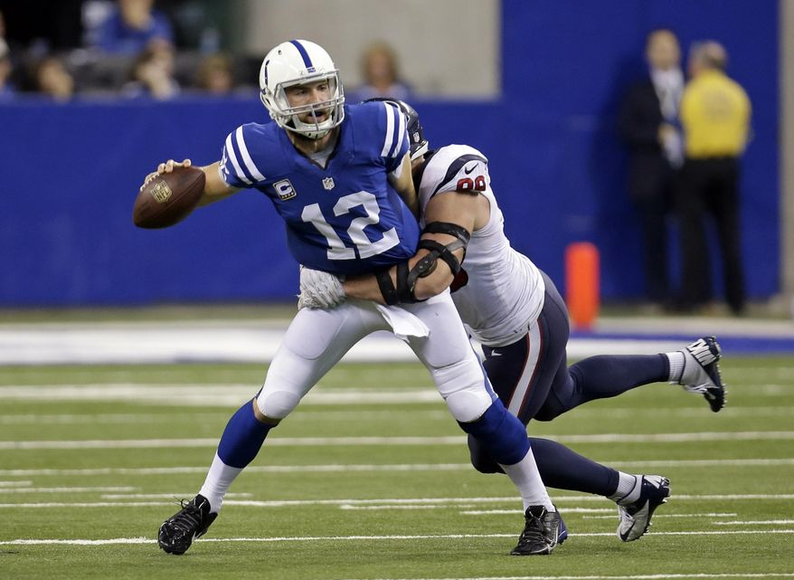 Houston Texans defensive end J.J. Watt, right, sacks Indianapolis Colts quarterback Andrew Luck during the first half of an NFL football game in Indianapolis, Sunday, Dec. 14, 2014. (AP Photo/AJ Mast)