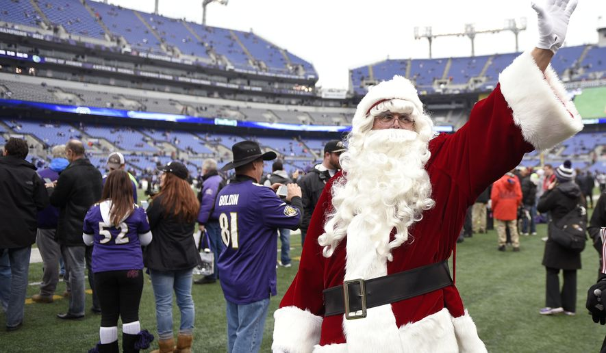 Santa Claus waves to the fans before an NFL football game between the Jacksonville Jaguars and the Baltimore Ravens in Baltimore, Sunday, Dec. 14, 2014. (AP Photo/Nick Wass)