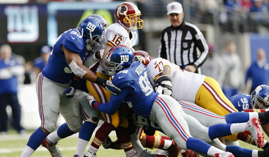 Washington Redskins quarterback Colt McCoy (16) gets wrapped up by New York Giants outside linebacker Devon Kennard (59) and defensive end Damontre Moore (98) during the first quarter of an NFL football game, Sunday, Dec. 14, 2014, in East Rutherford, N.J. (AP Photo/Julio Cortez)