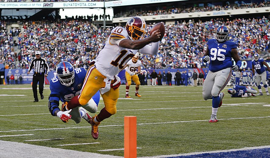 Washington Redskins quarterback Robert Griffin III (10) leaps for the goal line attempting to score a touchdown against New York Giants defensive end Jason Pierre-Paul (90) during the second quarter of an NFL football game, Sunday, Dec. 14, 2014, in East Rutherford, N.J. (AP Photo/Julio Cortez)