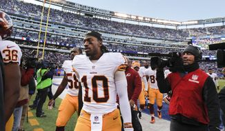 Washington Redskins quarterback Robert Griffin III (10) walks off the field at the end of the second quarter of an NFL football game against the New York Giants, Sunday, Dec. 14, 2014, in East Rutherford, N.J. (AP Photo/Julio Cortez)
