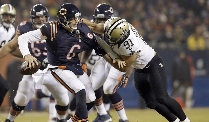 New Orleans Saints outside linebacker Kasim Edebali (91) grabs Chicago Bears quarterback Jay Cutler (6) during the first half of an NFL football game Monday, Dec. 15, 2014, in Chicago. (AP Photo/Nam Y. Huh)