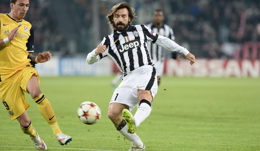 Juventus' Andrea Pirlo, right, challenges the ball with Atletico' Mario Mandzukic during a Champions League, Group A, soccer match between Juventus and Atletico de Madrid at the Juventus stadium in Turin, Italy, Tuesday, Dec. 9, 2014. (AP Photo/Massimo Pinca)