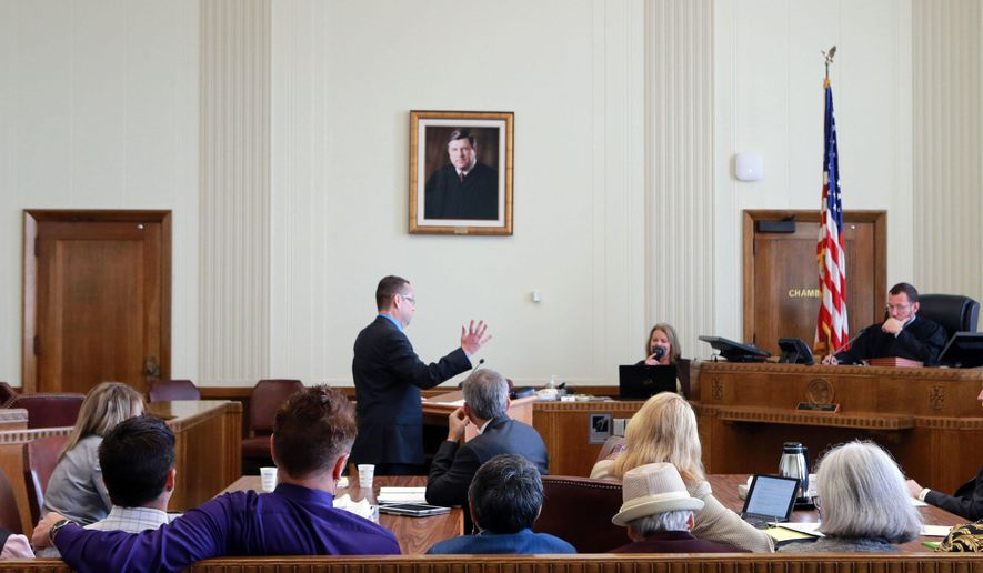 FILE - In this Thursday, Sept. 25, 2014 file photo, same-sex couples, plaintiffs in a class-action lawsuit against the state of Missouri, foreground, watch as Anthony Rothert, legal director of the American Civil Liberties Union of Missouri argues before Circuit Court Judge J. Dale Youngs during a hearing in Kansas City, Mo. American Civil Liberties Union officials say they have begun a new and more aggressive effort to intervene in Missouri and Kansas over highly public issues like same-sex marriage, privacy and police policy. (AP Photo/St. Louis Post-Dispatch, Christian Gooden, Pool, File)