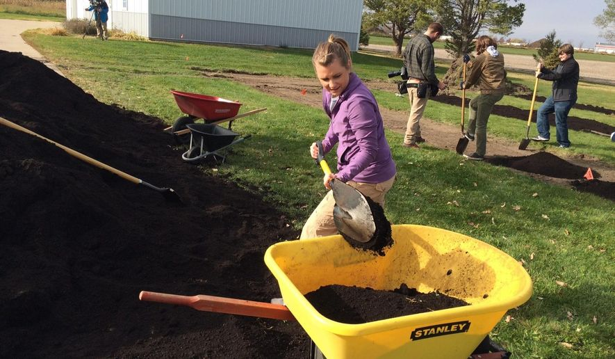 In this Nov. 2014 photo, Devon Leslie, a North Liberty Community Pantry student intern, works to prepare soil at the site where the pantry will plant its teaching garden in North Liberty, Iowa. The eastern Iowa charity said it's raised enough money to build a community teaching garden, which is expected to be a source of fresh produce for the more than 500 families it serves. The North Liberty Community Pantry raised nearly $39,000 to receive a matching grant from the Wellmark Foundation, the Iowa City Press-Citizen reported.(AP Photo/Sara Langenberg special to the Iowa City Press-Citizen)