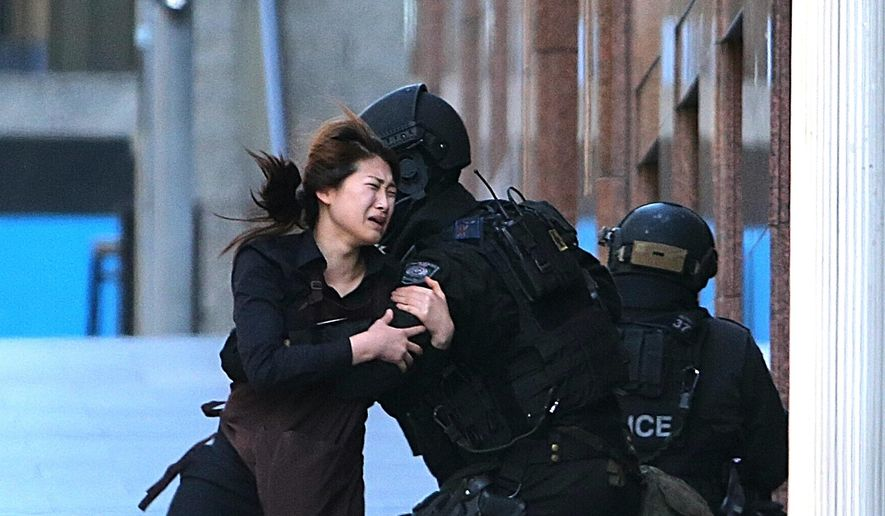 A hostage runs to armed tactical response police officers for safety after she escaped from a cafe under siege at Martin Place in the central business district of Sydney, Australia, Monday, Dec. 15, 2014. New South Wales state police would not say what was happening inside the cafe or whether hostages were being held. But television footage shot through the cafe's windows showed several people with their arms in the air. (AP Photo/Rob Griffith)