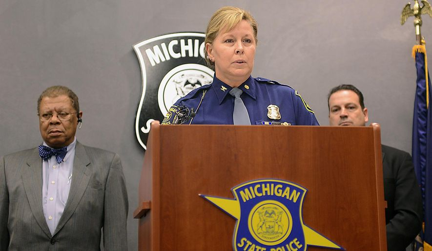Col. Kristie Kibbey Etue, Director of the Michigan State Police, speaks at the MSP headquarters in Lansing, Mich., Monday, Dec. 15, 2014, at a news conference announcing the arrest and charges against John C. Kelsey II for his alleged role in the death of Ingham County Sherrif's Deputy Grant Whitaker. Kelsey is facing charges of driving with a suspended or revoked license causing death and first-degree fleeing police. Ingham County Prosecutor Stuart Dunnings III, left, also spoke at the news conference. (AP Photo/Lansing State Journal, Dave Wasinger)