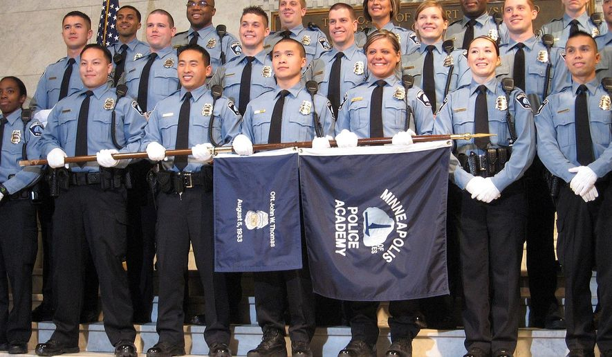 In a Thursday, Dec. 17, 2009 photo, the Minneapolis Police Academy class of 2009 pose during their graduation ceremony. Police departments in Minnesota and across the country could benefit from hiring more female officers, according to some women's advocates.They say a larger amount of female officers on a force can help diffuse tension between police and the public. (AP Photo/MPR News, Brandt Williams)
