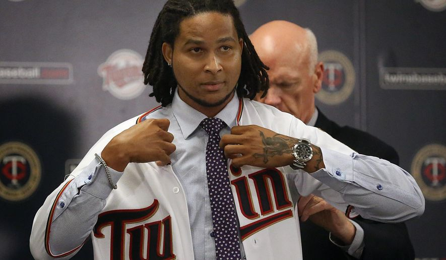 In this Dec. 13, 2014 photo, new Minnesota Twins pitcher Ervin Santana puts on a jersey as he is introduced during a baseball news conference in Minneapolis. (AP Photo/The Star Tribune, Jim Gehrz)