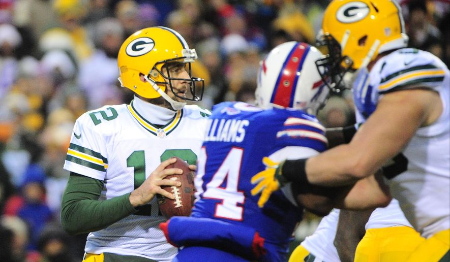 Green Bay Packers quarterback Aaron Rodgers (12) looks down field as Buffalo Bills' Mario Williams (94) rushes him during the second half of an NFL football game Sunday, Dec. 14, 2014, in Orchard Park, N.Y. Williams sacked Rodgers on the play leading to a safety. The Bills won the game 21-13.(AP Photo/Gary Wiepert)