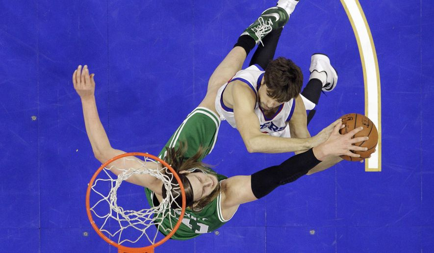 Philadelphia 76ers' Alexey Shved, of Russia,, right, tries to get a shot past Boston Celtics' Kelly Olynyk during the first half of an NBA basketball game, Monday, Dec. 15, 2014, in Philadelphia. (AP Photo/Matt Slocum)