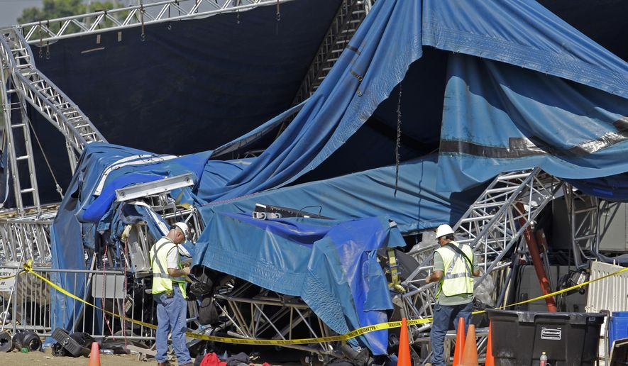 FILE - In this file photo taken on Wednesday, Aug. 17, 2011, investigators examine the stage that collapsed on Saturday at the Indiana State Fair in Indianapolis. Attorneys for a 13-year-old victim of the 2011 Indiana State Fair stage collapse are arguing the state's cap on liability damages is unconstitutional and should be thrown out by the Indiana Court of Appeals, Monday, Dec. 15, 2014. (AP Photo/Darron Cummings)