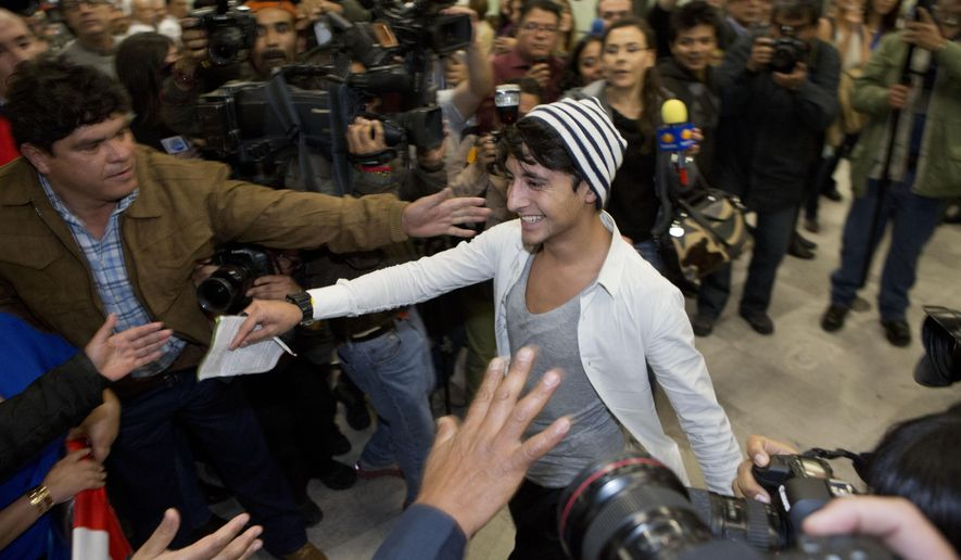 Adan Cortes Salas, the Mexican student who disrupted the Nobel Peace Prize ceremony in Oslo last week, walks toward his waiting family, as he arrives at the airport in Mexico City after being deported from Norway, Monday, Dec. 15, 2014. Lawyer Jens-Ove Hagan said Cortes Salas was deported Monday after Norwegian immigration officials rejected his application for political asylum. (AP Photo/Rebecca Blackwell)