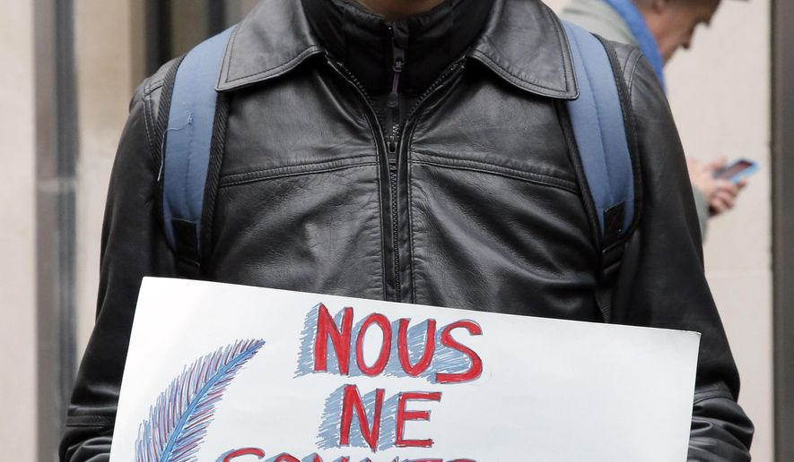 "Native American, from the Kichwa Guarani tribe, named Jackson, holds a banner reading ""We are not for sale"" outside of the Drouot's auction house in protest  at the auction of Native American Navajo tribe masks in Paris, Monday Dec. 15, 2014. Navajo officials have spent several hundred thousand euros to buy back seven tribal masks put up for sale at a disputed auction despite the U.S. Embassy in Paris asking Drouot to suspend the sale to allow Navajo and Hopi representatives to determine where they came from. (AP Photo/Francois Mori )"