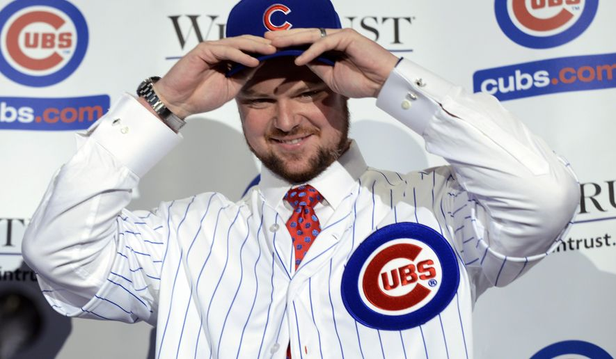 Pitcher Jon Lester puts on a Chicago Cubs jersey and hat after being introduced as a member of the Chicago Cubs baseball team during a news conference in Chicago, Monday, Dec. 15, 2014. Lester agreed to a $155 million, six-year contract with the Cubs at the winter meetings last week that set baseball records for largest signing bonus and biggest upfront payment. (AP Photo/Paul Beaty)