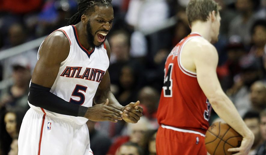 Atlanta Hawks' DeMarre Carroll, left, celebrates as Chicago Bulls' Mike Dunleavy, right, called a timeout after being defended by Carroll on an inbound pass in the first quarter of an NBA basketball game, Monday, Dec. 15, 2014, in Atlanta. Atlanta won 93-86. (AP Photo/David Goldman)