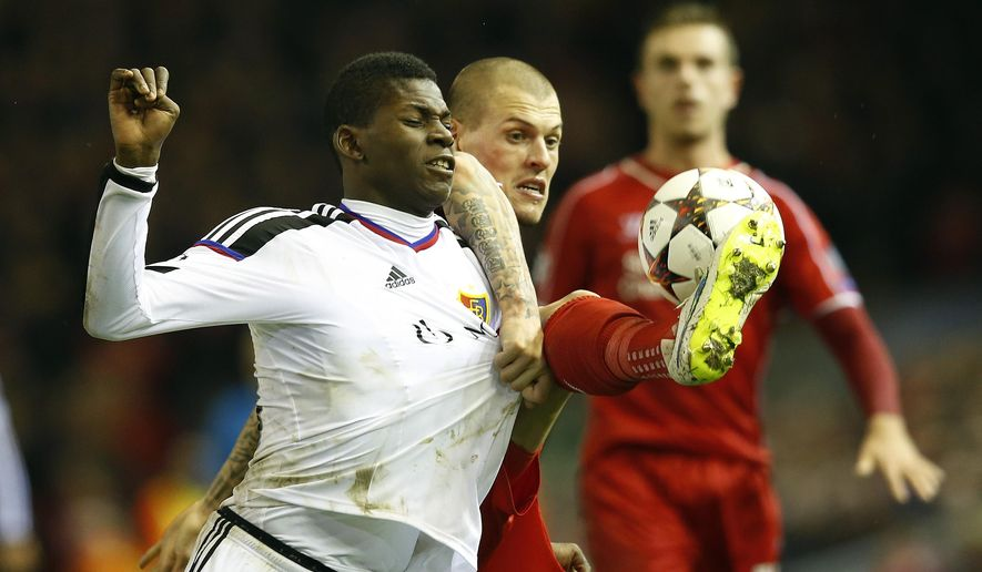 Basel's Breel Embolo, left, is challenged by Liverpool's Martin Skrtel during the Champions League Group B soccer match between Liverpool and FC Basel at Anfield Stadium in Liverpool, England, Tuesday, Dec. 9, 2014. (AP Photo/Jon Super)