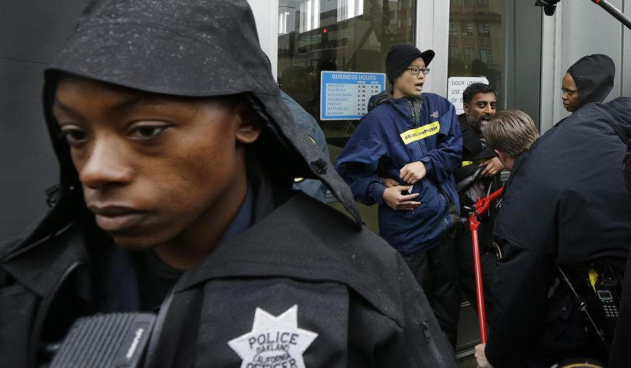 An Oakland police officer stands guard at the front door of police headquarters as another uses bolt cutters to free protestors who chained themselves to it Monday, Dec. 15, 2014, in Oakland, Calif. Demonstrators blocked streets around Oakland police headquarters and chained themselves to the front of the building Monday to protest recent grand jury decisions not to indict white officers who killed unarmed black men in Ferguson, Missouri, and New York. (AP Photo/Ben Margot)