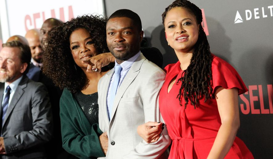"Producer Oprah Winfrey, left, poses with actors David Oyelowo and Carmen Ejogo at the premiere of ""Selma"" at the Ziegfeld Theatre in New York on Sunday, Dec. 14, 2014. (Photo by Evan Agostini/Invision/AP)"