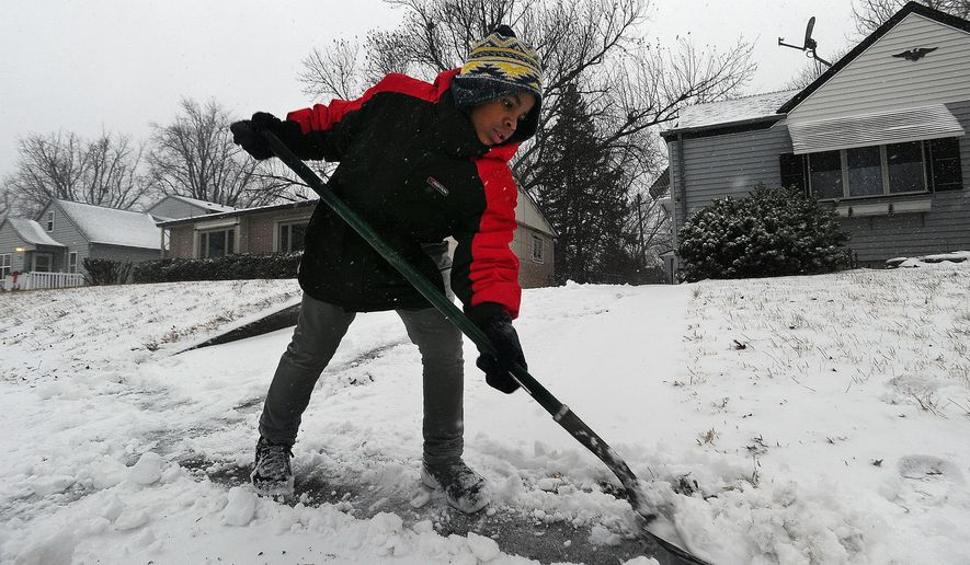 Marcus Jackson shovels the sidewalk outside of his Sioux Falls, S.D. home on Monday, Dec. 15, 2014. (AP Photo/Argus Leader, Jay Pickthorn)