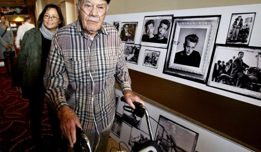 FILE - This Feb. 8, 2005 file photo, photographer Phil Stern walks past a gallery of photographs in Los Angeles, that he took of the late actor James Dean. Stern, the award-winning photographer who lugged his camera into combat during World War II and later became known for candid shots of Hollywood stars, died died Saturday, Dec. 13. 2014, in Los Angeles. He was 95. (AP Photo/Ric Francis,File)