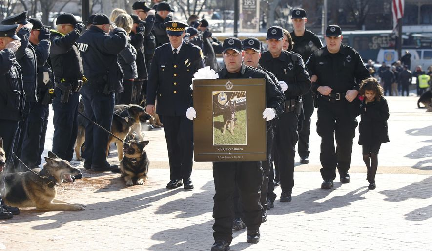 FILE - In this file photo from Feb. 7, 2014, officer Phil Lerza, second from right, walks with his family behind fellow Pittsburgh police officers carrying a photo of Lerza's K9 partner, Rocco, center, during the funeral procession in Pittsburgh. John Rush, 22, who was on trial for stabbing and killing the Pittsburgh police dog and injuring officers was found guilty Monday, Dec. 15, 2014, on 11 of 12 charges against him. (AP Photo/Keith Srakocic, FILE)