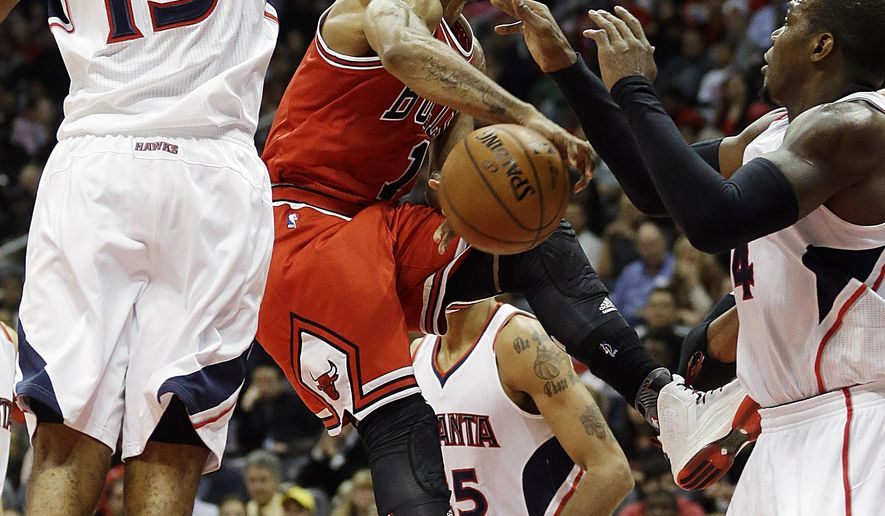 Chicago Bulls' Derrick Rose, center, is defended by Atlanta Hawks' Al Horford, left, and teammate Paul Millsap, right, in the third quarter of an NBA basketball game, Monday, Dec. 15, 2014, in Atlanta. Atlanta won 93-86. (AP Photo/David Goldman)