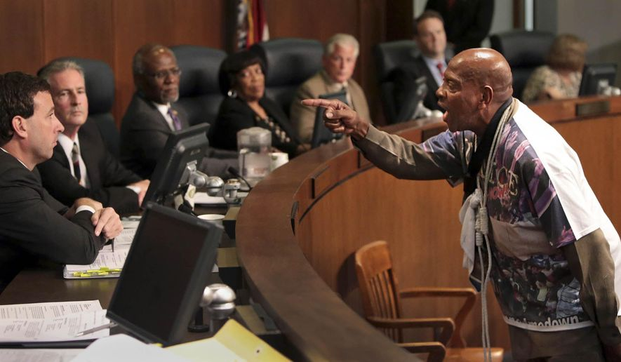 FILE - In this Tuesday, Sept. 16, 2014 file photo, St. Louis activist Anthony Shahid, right, confronts councilman Steve Stenger during the St. Louis County Council, in Clayton, Mo. Discussions of the city of St. Louis re-entering St. Louis County have been paused by the unrest in Ferguson that followed the shooting death of Michael Brown by a Ferguson police officer. St. Louis County Executive-elect Steve Stenger says he's coming into a job that demands a change in St. Louis County government. (AP Photo/St. Louis Post-Dispatch, Robert Cohen, File)
