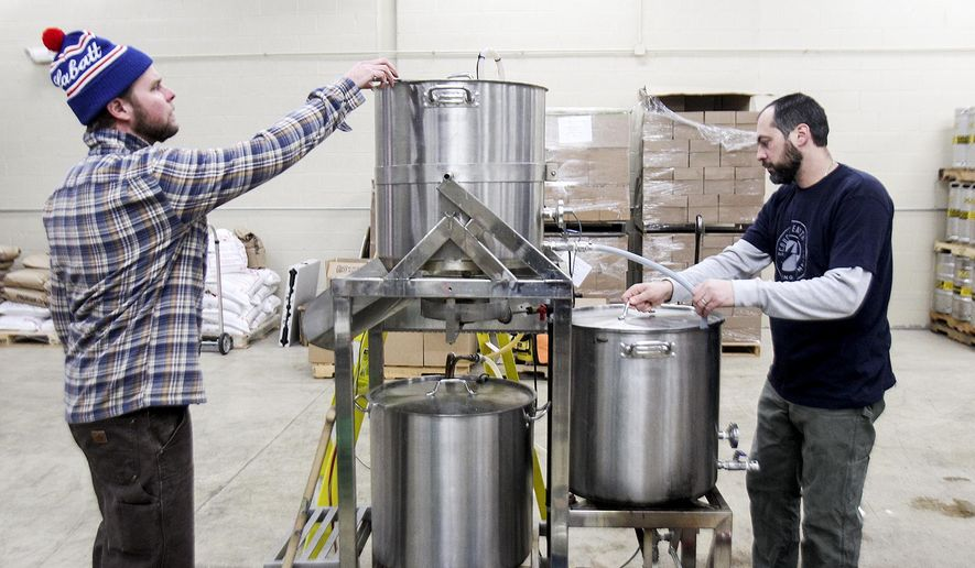 In this Wednesday, Dec. 10, 2014 photo, Dan Payson, head brewer, left, and Mark Gres, production assistant, extract sugar from malted barley while brewing a batch of beer at Scorched Earth Brewing in Algonquin, Ill. Several microbreweries in suburban Chicago share grain left over from the brewing process with local farmers, who can use it to feed their animals, instead of throwing it away. Sandy Robertson, a farmer who lives near Sycamore, receives spent grains from five microbreweries around the Chicago area, including Scorched Earth Brewing. (AP Photo/Northwest Herald, Sarah Nader)  MANDATORY CREDIT
